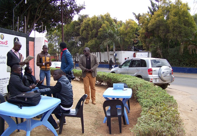 "Journalists from Zambia's The Post, working from their ""mobile newsroom"" on the street outside the publication's shuttered offices on July 13, 2016. The newspaper has continued to publish a truncated print version since Zambia's Revenue Authority seized its assets and closed its offices in June 2016. Photo: IPI"